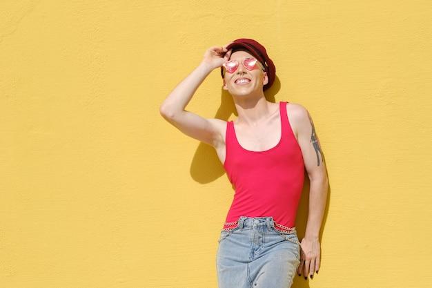 Junges nicht-binäres modell, das lächelt, während es draußen an einer gelben wand posiert. konzept der gleichstellung, vielfalt und nicht-binäres geschlecht.