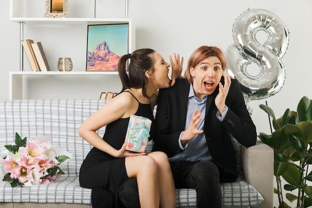 Junges paar am glücklichen frauentag, der das gegenwärtige wütende mädchen hält, flüstert dem kerlohr zu, das auf dem sofa im wohnzimmer sitzt