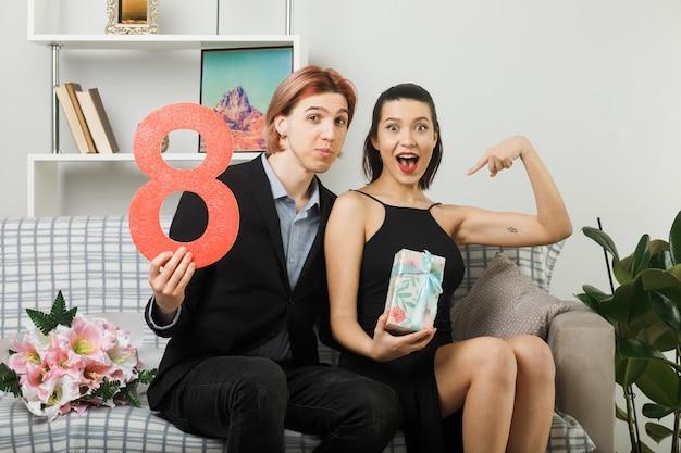 Junges paar am glücklichen frauentag, der die nummer acht mit geschenk auf dem sofa im wohnzimmer hält