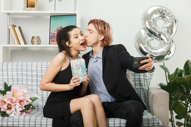 Junges paar am glücklichen frauentag, der geschenk hält, macht ein selfie, das auf dem sofa im wohnzimmer sitzt