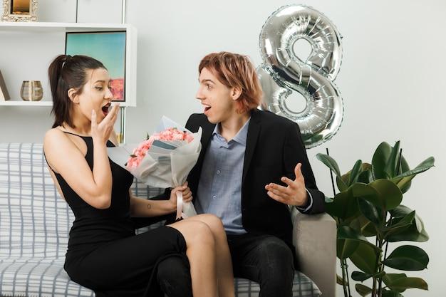 Junges paar am glücklichen frauentag mit blumenstrauß, der auf sofa im wohnzimmer sitzt