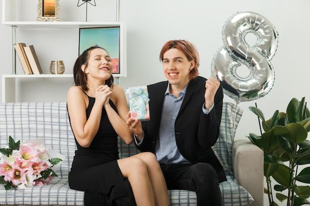 Junges paar am glücklichen frauentag mit geschenk auf dem sofa im wohnzimmer sitzend
