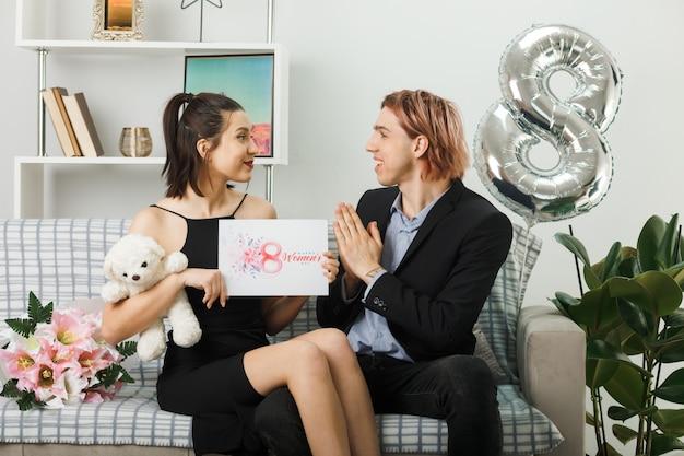 Junges paar am glücklichen frauentag mit teddybär und postkarte auf dem sofa im wohnzimmer sitzend