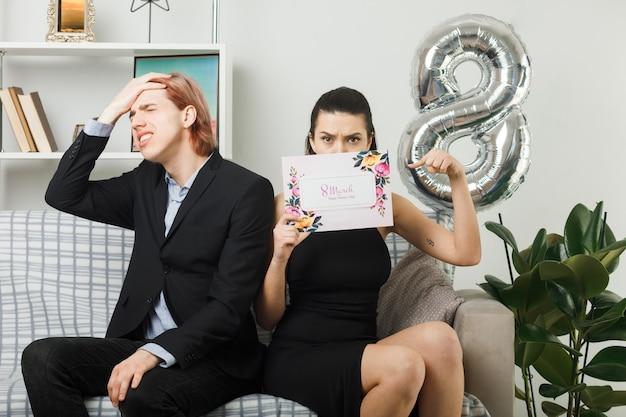 Junges paar am glücklichen frauentag strenge frau hält und bedecktes gesicht mit postkarte bedauert, dass der mann die hand auf die stirn legt und auf dem sofa im wohnzimmer sitzt?