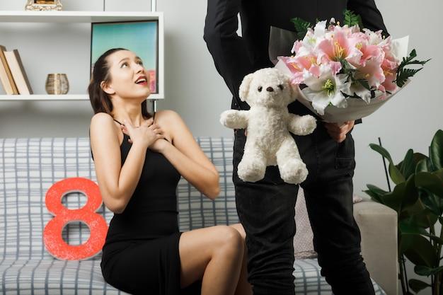Junges paar am glücklichen frauentag überraschtes mädchen, das auf dem sofa sitzt, der teddybär mit blumenstrauß an der taille im wohnzimmer hält