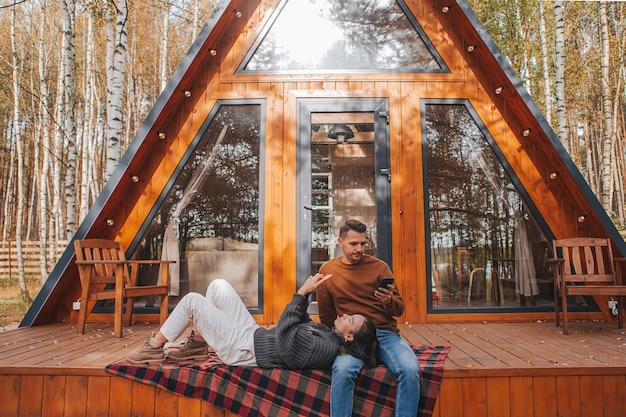 Junges paar am herbstlichen warmen tag auf der terrasse ihres hauses