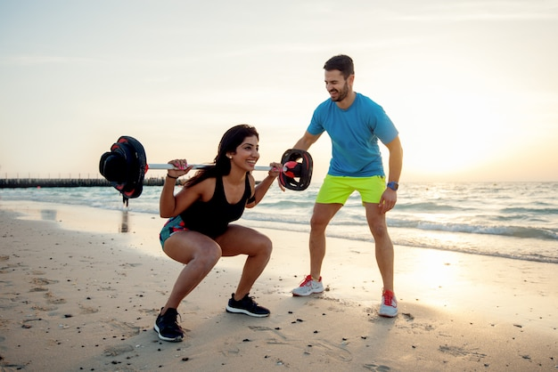 Junges paar am strand, trainierend.