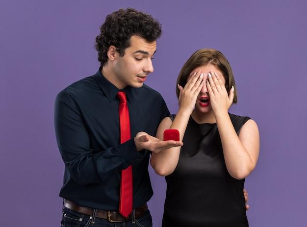Junges paar am valentinstag aufgeregter mann, der einer frau einen verlobungsring gibt, der den ring anschaut, eine neugierige frau, die die augen mit den händen isoliert auf der lila wand bedeckt?