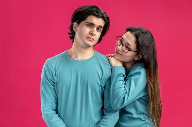 Junges paar am valentinstag erfreutes mädchen, das traurigen kerl einzeln auf rosafarbenem hintergrund betrachtet