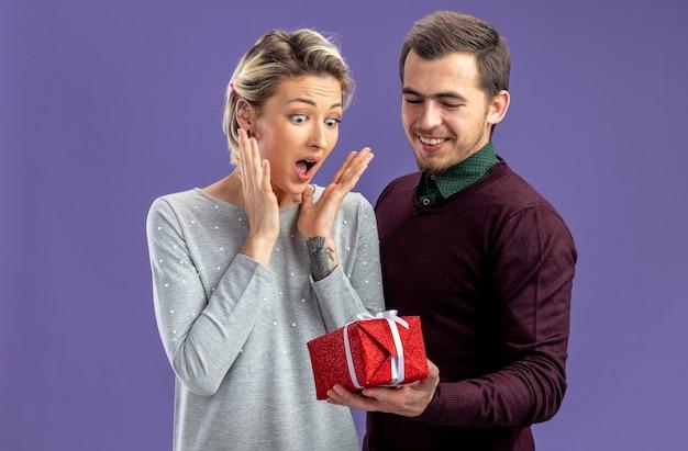 Junges paar am valentinstag freut sich über einen glücklichen kerl, der einem aufgeregten mädchen auf blauem hintergrund eine geschenkbox gibt