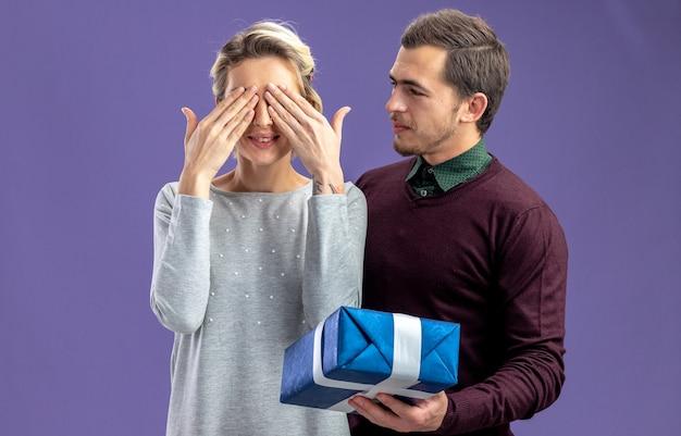 Junges paar am valentinstag freut sich über einen mann, der dem mädchen eine geschenkbox gibt, die auf blauem hintergrund isoliert ist