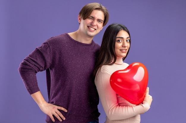 Junges paar am valentinstag lächelnder kerl, der neben mädchen mit herzballon auf blauem hintergrund steht