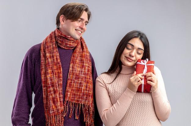 Junges paar am valentinstag lächelnder kerl, der zufriedenes mädchen mit geschenkbox auf weißem hintergrund betrachtet