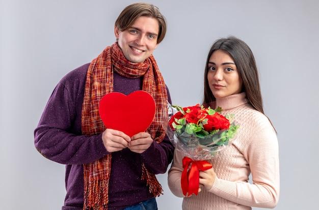 Junges paar am valentinstag lächelnder kerl mit herzförmigem kasten erfreutes mädchen mit blumenstrauß isoliert auf weißem hintergrund