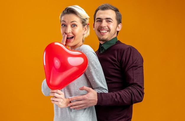 Junges paar am valentinstag lächelnder kerl umarmte lachendes mädchen mit herzballon isoliert auf orangem hintergrund