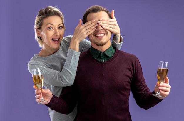 Junges paar am valentinstag - lächelndes mädchen bedeckte kerl etes mit gläsern champagner isoliert auf blauem hintergrund