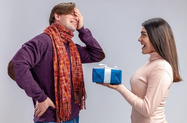 Junges paar am valentinstag lächelndes mädchen, das dem weinenden kerl eine geschenkbox gibt, die auf weißem hintergrund isoliert ist