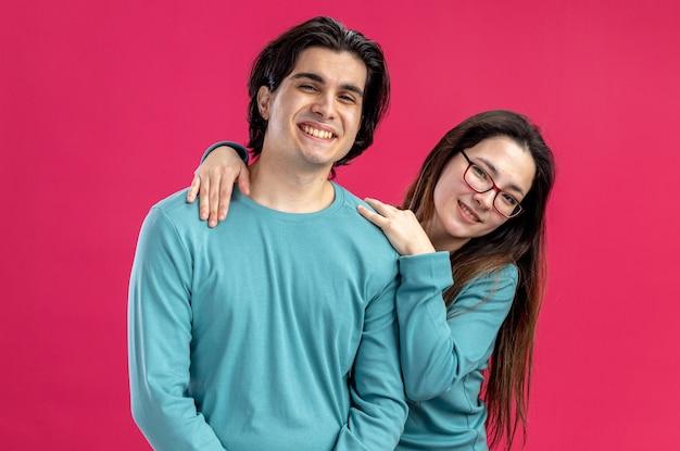 Junges paar am valentinstag lächelndes mädchen umarmte lächelnden kerl isoliert auf rosa hintergrund