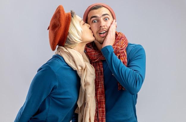 Junges paar am valentinstag mit hut mit schal erfreutes mädchen, das überraschten kerl küsst, isoliert auf weißem hintergrund