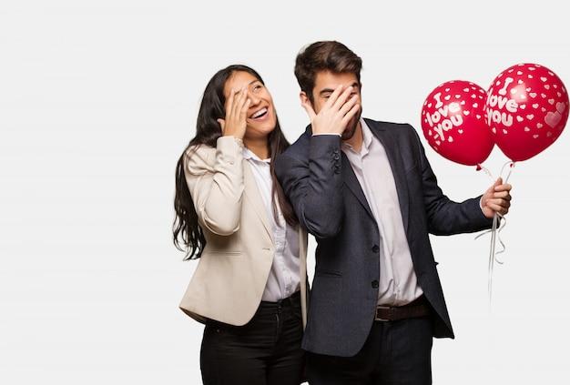 Junges paar am valentinstag verlegen und gleichzeitig lachend