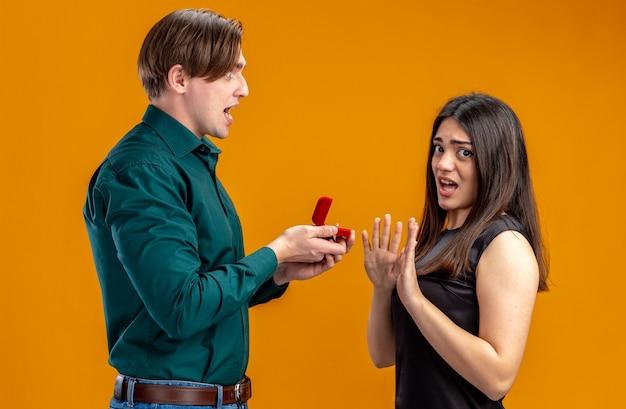 Junges paar am valentinstag wütender kerl, der dem unzufriedenen mädchen ehering gibt, isoliert auf orangefarbenem hintergrund