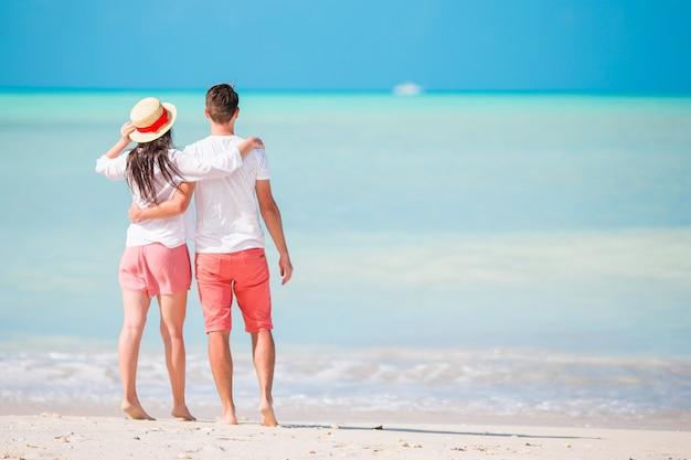 Junges paar am weißen strand. glückliche familie in den flitterwochenferien