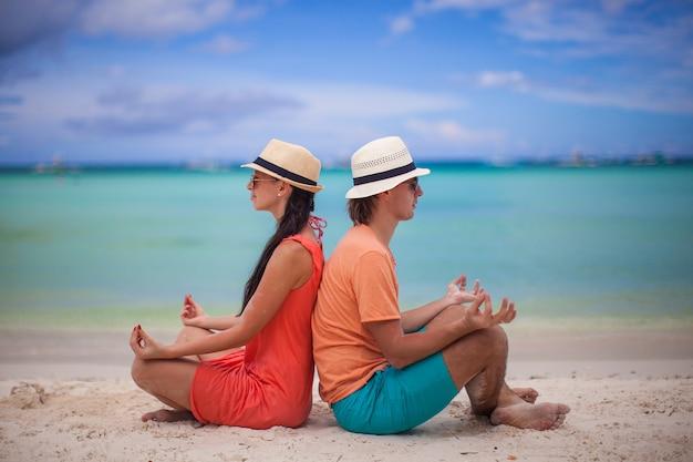 Junges paar amüsieren sich und yoga am strand