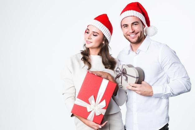 Junges paar an weihnachten in weihnachtsmannhüten mit geschenken