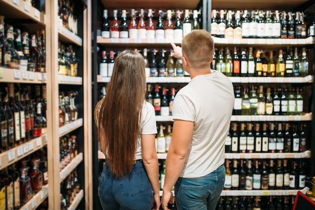Junges paar auf der suche nach wein im alkoholmarkt