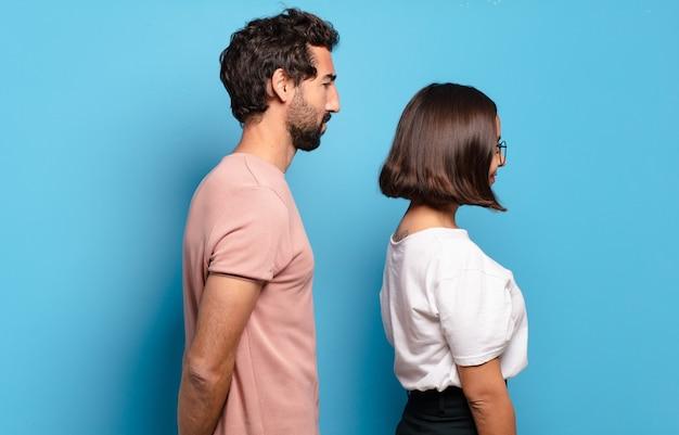 Junges paar auf profilansicht, das raum voraus kopiert, denkt, sich vorstellt oder träumt