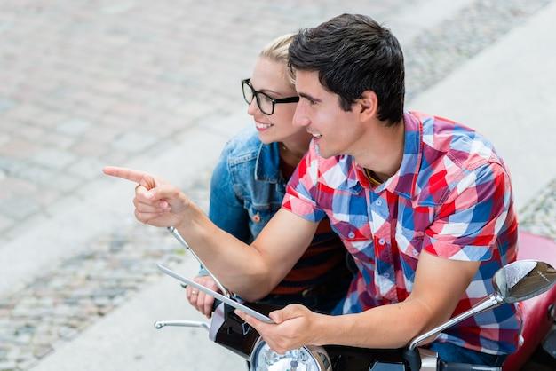 Junges paar auf städtereise in berlin, die ihre vespa-tour mit tablet-pc plant