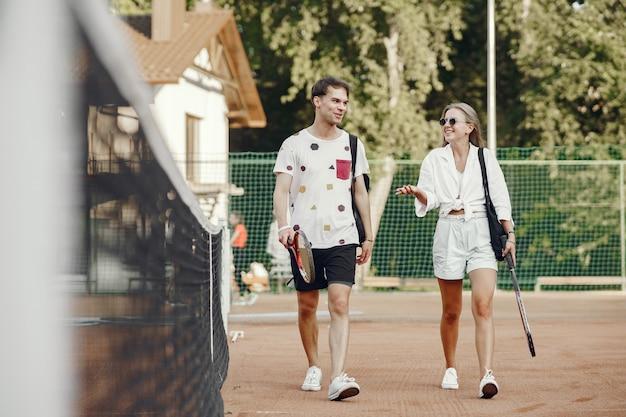 Junges paar auf tennisplatz. zwei tennisspieler in sportkleidung.