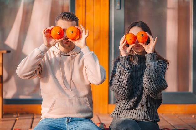 Junges paar bedeckte augen mit kürbissen am warmen herbsttag auf der terrasse ihres hauses