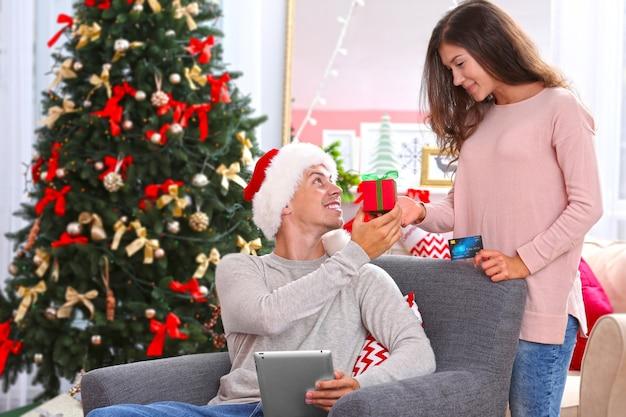 Junges paar beim online-shopping mit kreditkarte zu hause zu weihnachten