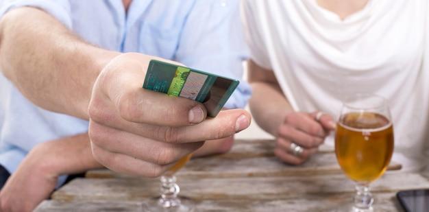 Junges paar bezahlt die getränkerechnung mit kreditkarte