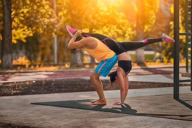 Junges paar, das akrobatische gymnastik im freien tut, das durch die wärme der morgensonne hinterleuchtet wird, die einen handstand aufteilt, spaltet sich in einem gesundheits- und fitnesskonzept