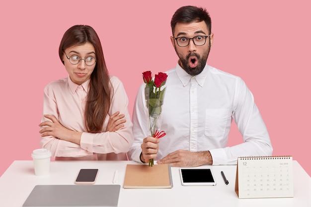 Junges paar, das am schreibtisch sitzt und mann, der blumenstrauß der rosen hält