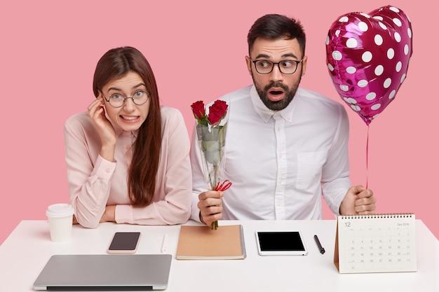 Junges paar, das am schreibtisch und am mann hält, der strauß der rosen und des herzförmigen ballons hält