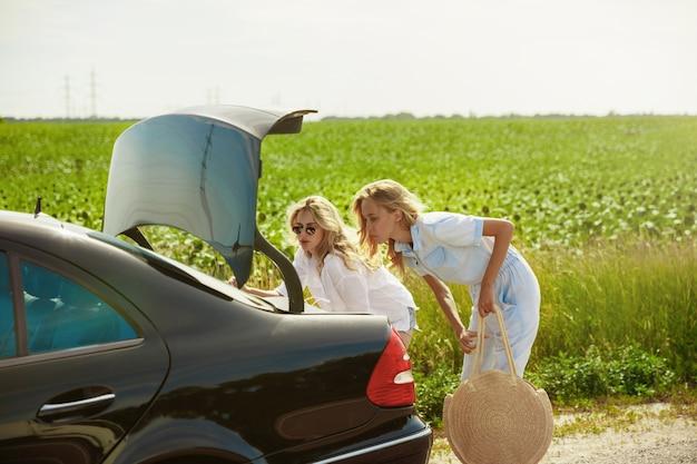 Junges paar, das an sonnigem tag auf urlaubsreise auf dem auto geht