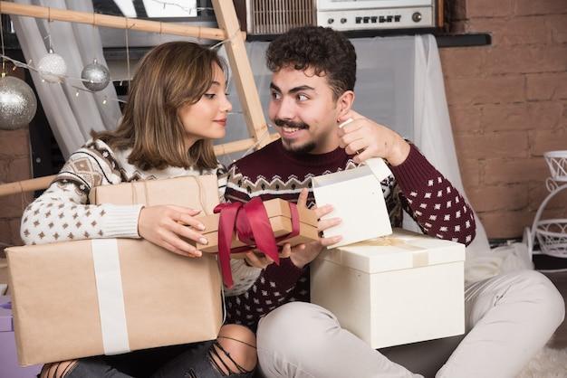 Junges paar, das auf dem boden mit kastengeschenken im weihnachtsinnenraum sitzt.