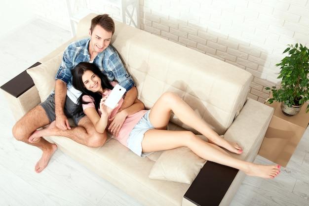 Junges paar, das auf dem sofa in der draufsicht des raumes liegt
