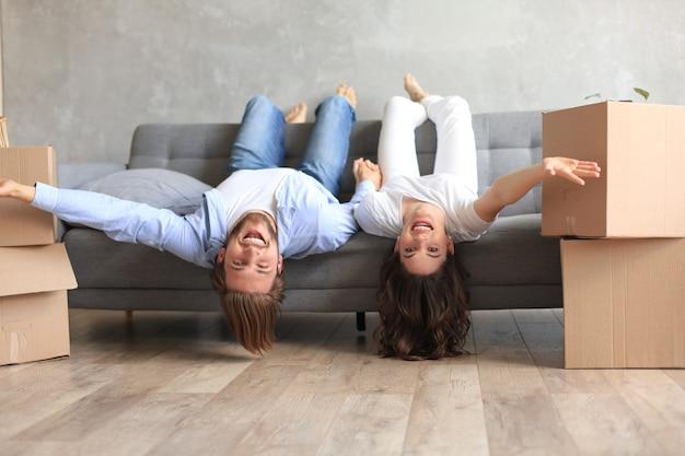 Junges paar, das auf dem sofa mit den köpfen liegt, die sich kopfüber entspannen und die kamera im wohnzimmer am umzugstag anlächeln.