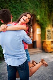 Junges paar, das auf der stadtstraße umarmt