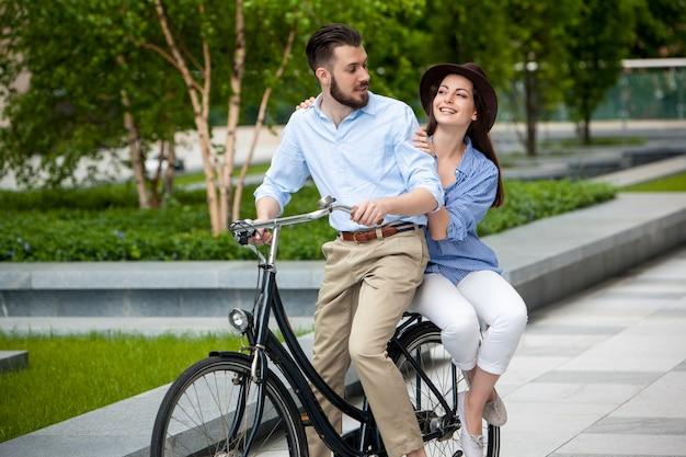 Junges paar, das auf einem fahrrad sitzt