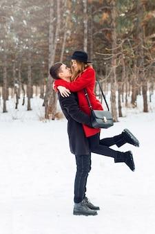 Junges paar, das auf einem schneebedeckten feld umarmt