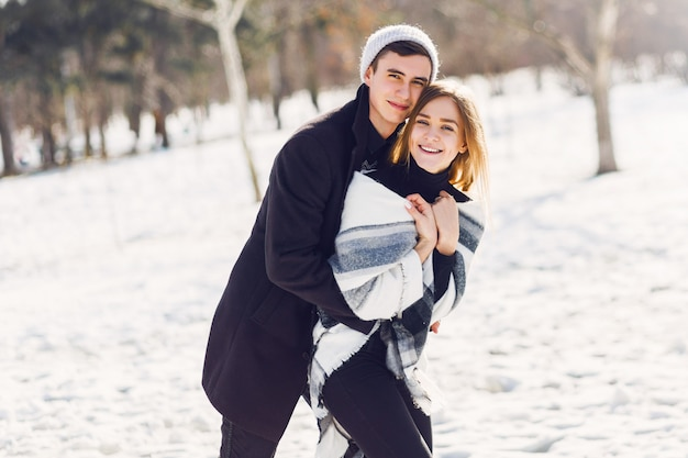 Junges paar, das auf einem verschneiten feld spielt