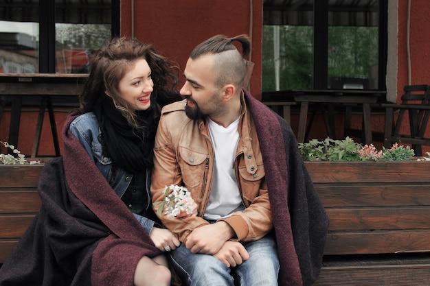 Junges paar, das auf einer bank in der alten stadtstraße sitzt. liebesgeschichte