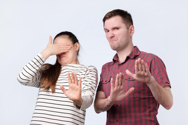 Junges paar, das auf etwas unangenehmes schaut, das mit händen gestikuliert, die sich weigern, es zu kaufen