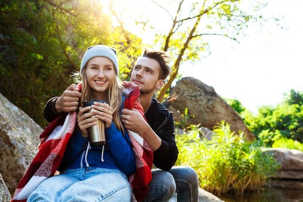 Junges paar, das auf felsen im canyon sitzt, lächelt und tee trinkt