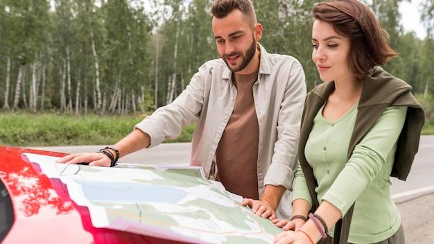 Junges paar, das auf karte auf der motorhaube des autos schaut